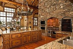 Love the wall of stone with built in ovens and range.  Also love the wagon wheel light fixture with hurricane lamps on top.