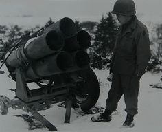 """A member of the 5th Infantry Division inspects a 5 barreled 21 cm Rocket Launcher """"Screaming Meemie"""" (Nebelwerfer) near Diekirch, Luxemburg"""