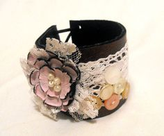 A tattered creamy colored wrist cuff with pieces of fabric, lace and ribbon, decorated with genuine burgundy swarovski crystal beads. Description from deviantart.com. I searched for this on bing.com/images