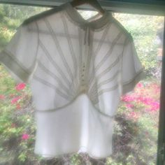 """Vintage Sheer Ivory Blouse Prettiest sheer cream blouse by Judy Bond circa 1950s. Sheer, no lining. Buttons up the back.  Tag size 34. I think best for modern m for a nice loose fit but can fit various sizes. Armpit 40""""   waist 31"""" Has a deco feel to me with the placement of the lace and romantic shape. Adorable rhinestone buttons. Sweet little bow at the collar. Layering dream. Great condition. Minor imperfections in the fabric due to age but free of notable stains/holes.  No trades/PP…"""