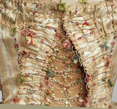 Close up of front bodice opening of ca 1775–80 robe a la francaise, showing decorative elements such as fly fringe, braid, cord, tiny tassels, ruching, and more.   probably British   The Met