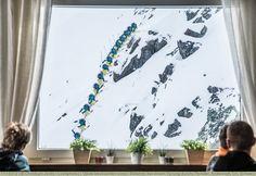 Gäste beobachten einen Skifahrer bei einem Sprung durchs Fenster, Andermatt, Uri, Schweiz