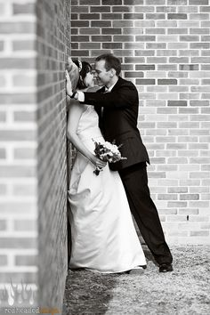 bride leans against wall/groom leans in for a kiss