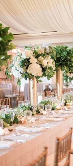 Gold vases with green and white flowers
