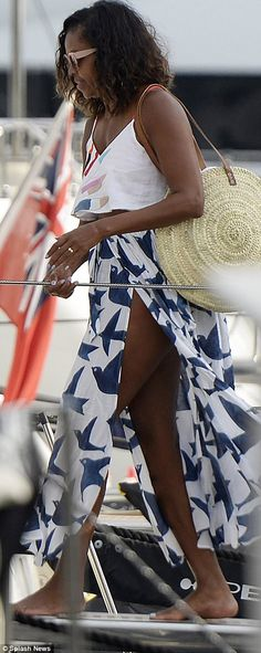 Travels: The former First Lady, 53, boarded a yacht on Friday, wearing a white crop top and a stylish wrap skirt with a bird pattern, letting the fabric flow to show her toned legs
