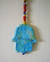 """Clay hamsa on a wall, inscribed with the Hebrew word """"behatzlacha"""" – literally """"in success"""", or """"good luck"""""""