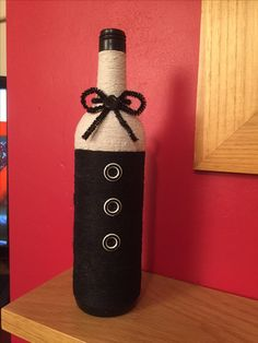 Wine bottle with Cream and Black string and button & pipe cleaner decoration . So pretty