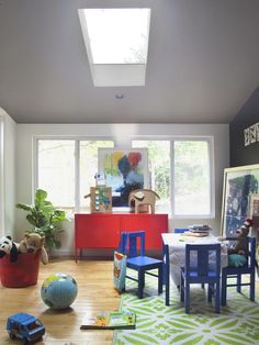 Screened-in porch turned playroom with a bright red storage unit. #red