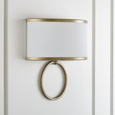 Shop Axiom Brass Sconce. We've updated a classic sconce style with contemporary contrast and clean geometry. Providing soft, indirect lighting, the sconce is anchored by single brass-finished ring topped with an off-white shade that's trimmed to match.