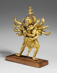 A Tibetan gilt bronze figure of Chakrasamvara in yab-yum. Possibly 19th century  A Tibetan gilt bronze figure of the four-headed and twelve-armed Chakrasamvara in alidhasana together in a divine embrance with his consort Vajravarahi. Attributes missing. Forearms cast separately, one missing. Possibly 19th century. Wooden base.  Height 31 cm