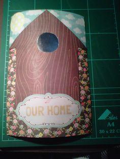 Esta hecho sobre un rollo de papel de cocina vacio e imita a los adornos que se hacen sobre una teja. Es una casita de pajaros con un pequeño papel que refleja la imagen de quien la mira y se puede usar para dar la bienvenida a tu casa a tus invitados