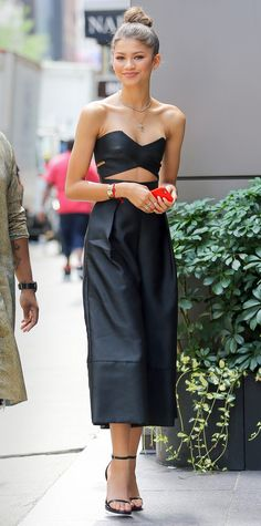 For a day out in New York City, Zendaya Coleman worked the jumpsuit trend in a black Solace London style, which featured a cutout bodice-like top and voluminous cropped trousers. Coleman kept the rest of her look minimal with an effortless top knot, simple strappy sandals, and an array of dainty gold jewelry.