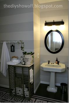 Gorgeous guest bathroom... stripes and painted floorand check out the lobster trap? for toilet tissue!clever!!