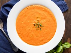 A creamy carrot soup flavored with cumin, ginger, and spicy North African harissa paste, with a toasted almond and parsley garnish.