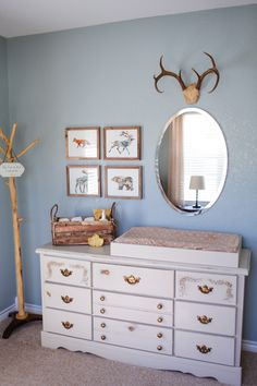 neutral nursery with light blue walls, dresser with gold knobs, change station, gold accents and cream