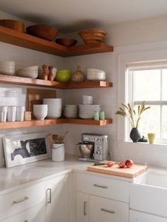 Tiny home cottage kitchen. These open shelves make use of the corner space, and are easy on the eyes, via Design Sponge
