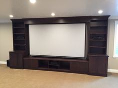 Dark brown shaker style entertainment center with bookcases and space for a tv or projector screen.