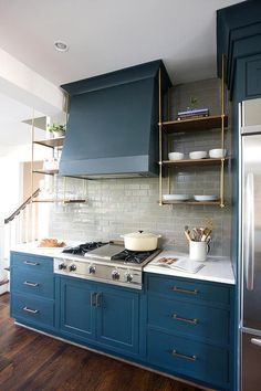 Beautiful kitchen features blue cabinets adorned with brass hardware paired with white marble countertops and a gray glass subway tiled backsplash.