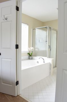 Cheap Bathroom Makeover | We updated the 1990s master bathroom in our suburban home for under $500 and gave it a fresh, spa look. Heres how we kept it on budget.   #bathroomideas #bathroommakeover #bathroomrenovation #budgetmakeover #budgethome #diyremodel #spabathroom #masterbathroom #whitebathroom #whitebathroomideas #traditionalbathroomdecor