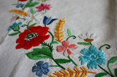 This is a beautiful Vintage linen blend ( I believe) tablecloth hand embroidered in the Hungarian Kalocsa folk art pattern. The edges are stunningly trimmed in a hand crochet lace floral trim blanket stitched to the tablecloth.  The square tablecloth is bordered by a gold dot and dash line and has embroidered florals on the four sides. The tablecloth has a beautiful bright floral garland in a circle in the middle.  This is a spectacular piece in perfect condition. Would make a nice gift…
