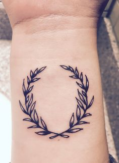 Olive wreath inner wrist tattoo. Meanings: peace, growth, victory.