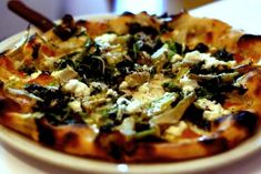 Pizza topped with nettles, artichoke, and sheep's milk ricotta. Made with local, healthy ingredients. #healthyfood