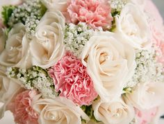 Close-up of a pink, white, and ivory bridal bouquet -- ivory roses, white baby's breath, and pink carnations.