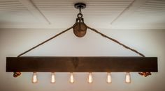 This rustic cedar beam with Edison bulbs is suspended by a barn pulley and 3/4 inch rope. The 6x6 beam is hand planed and sealed with the color of your choice to create a stunning focal point in your