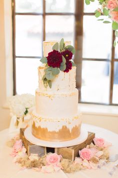 wedding cake with gold leaf and floral decor