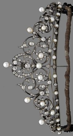 A diamond and pearl tiara, 1890 Designed as an openwork series of meandering foliate motifs, set throughout with rose, single, old brilliant and cushion-shaped diamonds, highlighted by 4.8-5.6mm pearls 'buds', diamonds approx. 5.80cts, one diamond deficient, pearls untested, length 20.0cm, fitted case