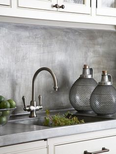 This traditional kitchen is updated with a brushed metallic backsplash. Due to its finish, the backsplash has a laid-back feel that correlates well with the rest of the kitchen hardware.