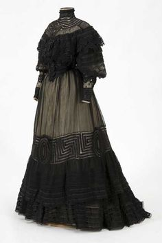 Black lace over ecru silk taffeta, two piece gown of Mrs. Cushman K. Davis, (Minn. Governor's Wife). Severe mono bosom bodice with high standing collar, dropped netted yoke with tucked lace and lace applique on silk. Modified leg of mutton sleeve. Center back closure. Skirt is wide gored lisse with fullness at center back and netted ribbon lace dropping into tucked ribbon lace flounces. Silk ruffled petticoat has lisse over petticoat.