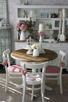 Cottage chic fresh white with raspberry accessories give this dining room a country modern feel; lots of light coloured accessories add charm making the room feeling cluttered and the dove grey and white damask wallpaper makes a perfect backdrop.