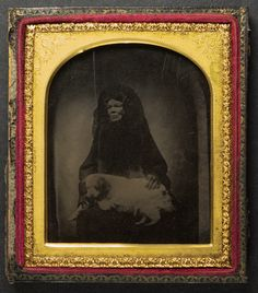 Early ambrotype of a cloaked lady and dog - Possibly a mourning image? Sixth-plate ambrotype. The mat is very thin metal supported by cardboard. Full case with broken hinge. The image is backed with black velvet.  It has a distinct feel to me as having been copied from an earlier image possibly a daguerreotype.