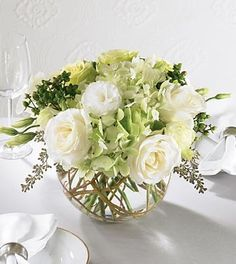 White and light green roses, gorgeous green hydrangea and green carnations along with white lisianthus accented with seeded eucalyptus and curly willow arranged in a clear glass bubble bowl. Your purc                                                                                                                                                                                 More