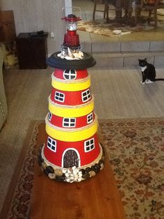 Clay pot lighthouse with shells and river rocks. Oh look, my cat Lucy has photobomb the shoot. :-)