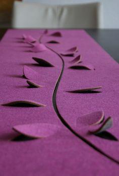 Extravaganter Tischläufer mit Blattkonturen.  Die Blätter können individuell gebogen und gerollt werden, oder auch wieder plan in ihre Aussparungen...