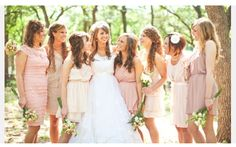 Non-matching bridesmaid dresses in dusty rose and campagnes.