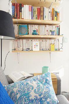 petit salon, canapé gris, coussins bleus, bibliothèque légère étagères bois