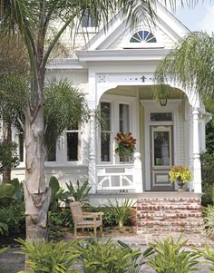 New Orleans Queen Anne Cottage: cut-out wooden trim, turned columns, a horizontal balustrade, and fish-scale shingles.