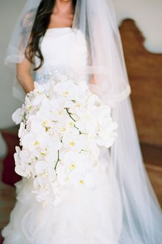 A cascading bouquet of phalaenopsis orchids | @THEGROVERS | Brides.com
