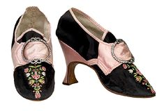 Embroidered black silk shoes, English, 1780-85  High heels reached their ascendancy in the 1770s and 80s. They also became more delicate in design and there was a preference for them to be set quite far back, directly under the heel. This style resulted in weakness under the instep. In order to compensate for this, many shoemakers employed wedge-like structures to help support the shank.