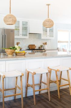 Rattan Pendant Lights above kitchen island with white and wood bar stools. Design by Rita Chan Interiors