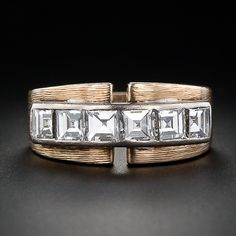 This is a bold and stylish wide two-tone band ring from the mid-twentieth century. Six glistening square step-cut diamonds are channel set across the top in white gold set atop a textured finish 14 karat yellow gold band. A comfortable, low profile ring with a bright white diamond flash.