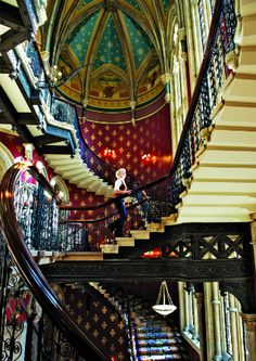 St. Pancras Hotel, London  ~This grand double staircase, with its original wrought-iron balustrade and vivid patterned carpeting, swirls up three stories of this Gothic Revival hotel adjacent to St. Pancras Station. It was lovingly restored in 2011, but much of its original late-19th-century character remains, from the vaulted gold-leaf ceiling to the red hand-stenciled wall designs.