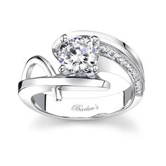 This modern unique engagement ring has a white gold by pass shank that curves around the prong set diamond center. One shoulder is accented with pave set diamonds decorating the inside wall, while the other shoulder has a round wire trim rising from the bottom of the shank and meeting at the top.   Available in two-tone, 18k or platinum.