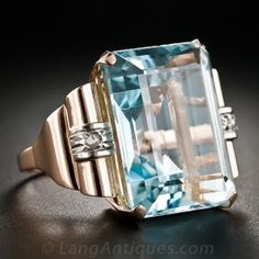 A serene glacier-blue aquamarine, weighing in at about 23 carats, glistens between a pair of scrolled shoulders, banded in 18 karat gold and dotted with a tiny rose-cut diamond, in this classic Retro cocktail ring, crafted in radiant rose gold - circa 1940s. This bright and beautiful bauble measures 13/16 inch by 7/8 inch-plus wide.