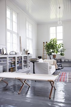 Like the FEEL of this room: painted grey floor, big fiddle leaf fig, stripped cotton rug (good color) glass front book cases, slip covered (white) sofa, rocking chair, TALL windows: combine to create cool mix of different styles that feel much like my own. But where'z the art??