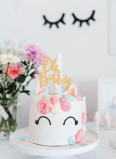 Un beau gâteau licorne avec un cake topper Oh Baby shower