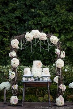 beautiful rustic twig arch at wedding over cakes. dahlia decorated and strings of pearls just beautiful